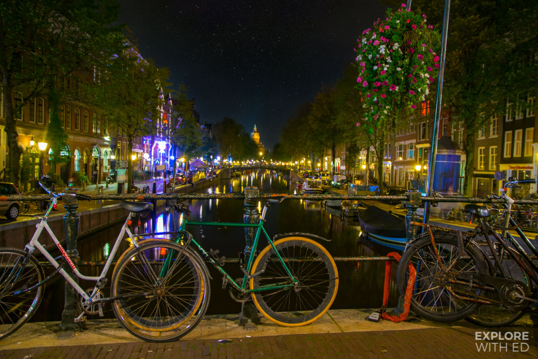 Bicycles lining Amsterdam's canal bridges at night looking towards Centraal