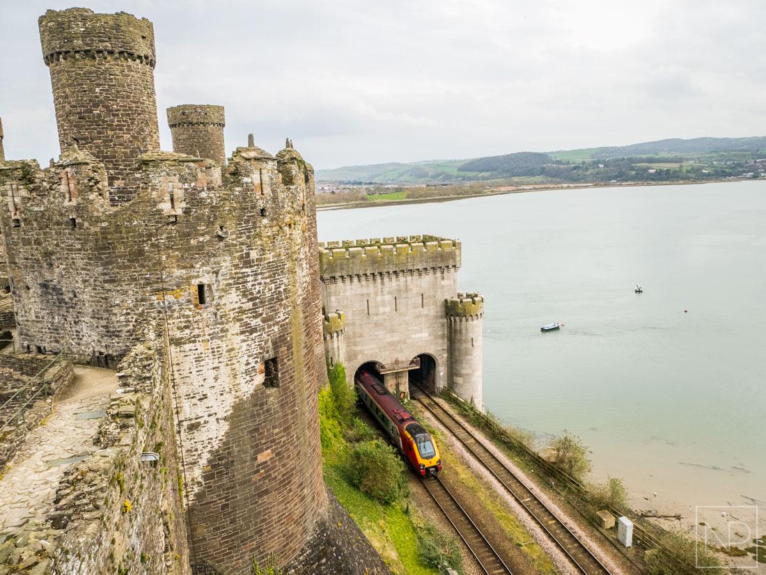 Train passing alongside Conwy Castle and suspension bridge